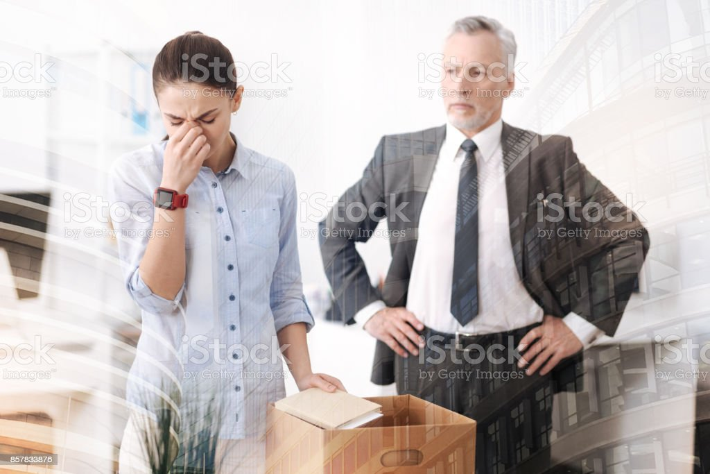 Strict boss dismissing a young sad woman stock photo
