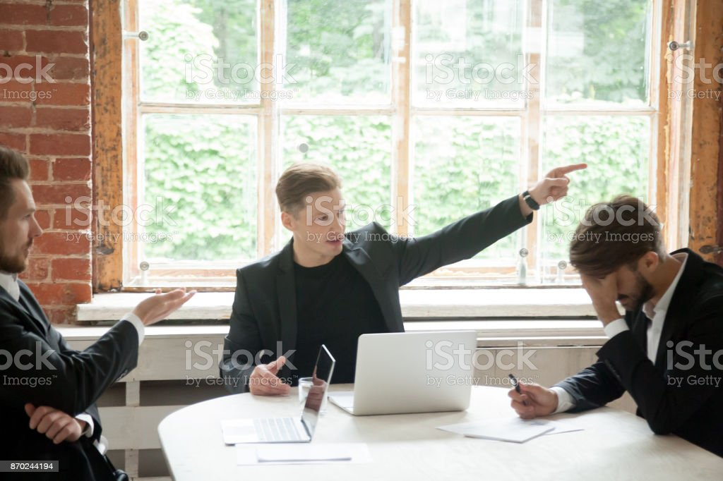 Strict boss telling upset employee to leave room during briefing. stock photo