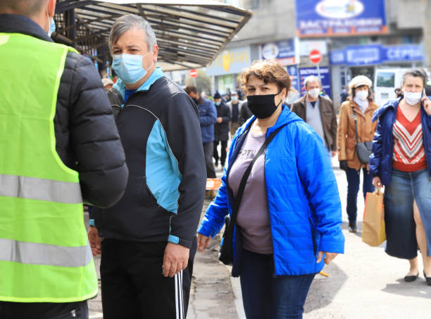 Strict control of people waiting in line for marketplace, wearing face masks stock photo