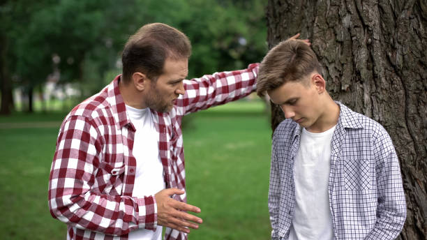 Strict dad scolding son for bad marks at school, parent respect, upbringing Strict dad scolding son for bad marks at school, parent respect, upbringing punishment stock pictures, royalty-free photos & images