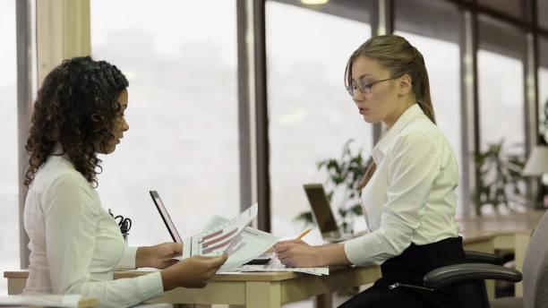 strenge weibliche teamleiter prüfung papiere mit mitarbeiter, brainstorming-projekt - soziologie stock-fotos und bilder