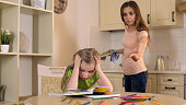 Strict mother criticizing daughter for mistakes in homework, lack of support, stock footage