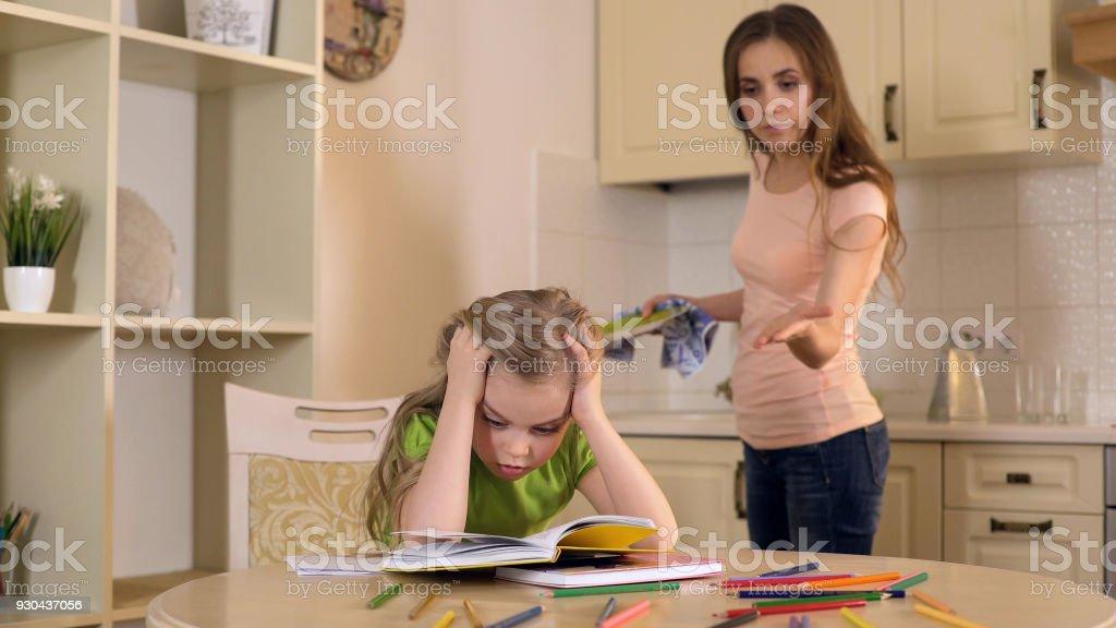 Strenge Mutter Tochter zu kritisieren, denn Fehler in Hausaufgaben, mangelnde Unterstützung – Foto