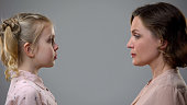 istock Strict mother looking scared daughter on grey background, discipline upbringing 1162337006