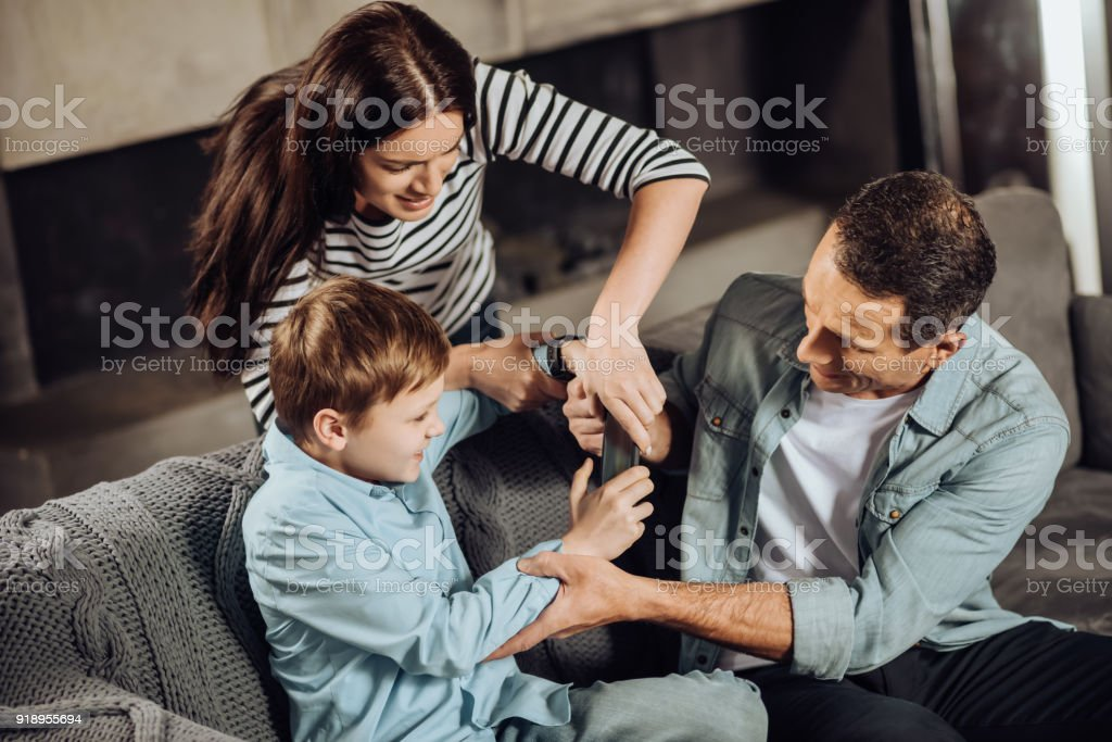 Strict Parents Taking Away Phone From Sons Hands Stock Photo