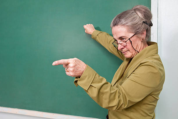 Strict teacher pointing at student stock photo
