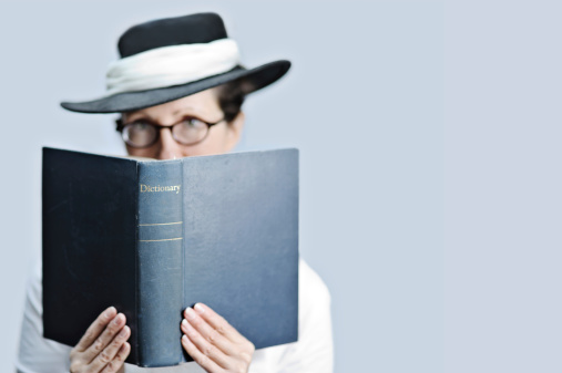 ** Very shallow DOF - focus on word 'dictionary'.** Prim lady librarian/teacher/editor/crossword fanatic/scrabble player/bookworm wearing glasses and Edwardian style hat, holding dictionary and looking at viewer.