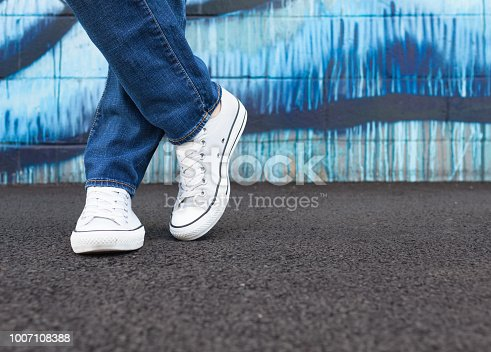 Person in jeans and shoes posing up against a wall.