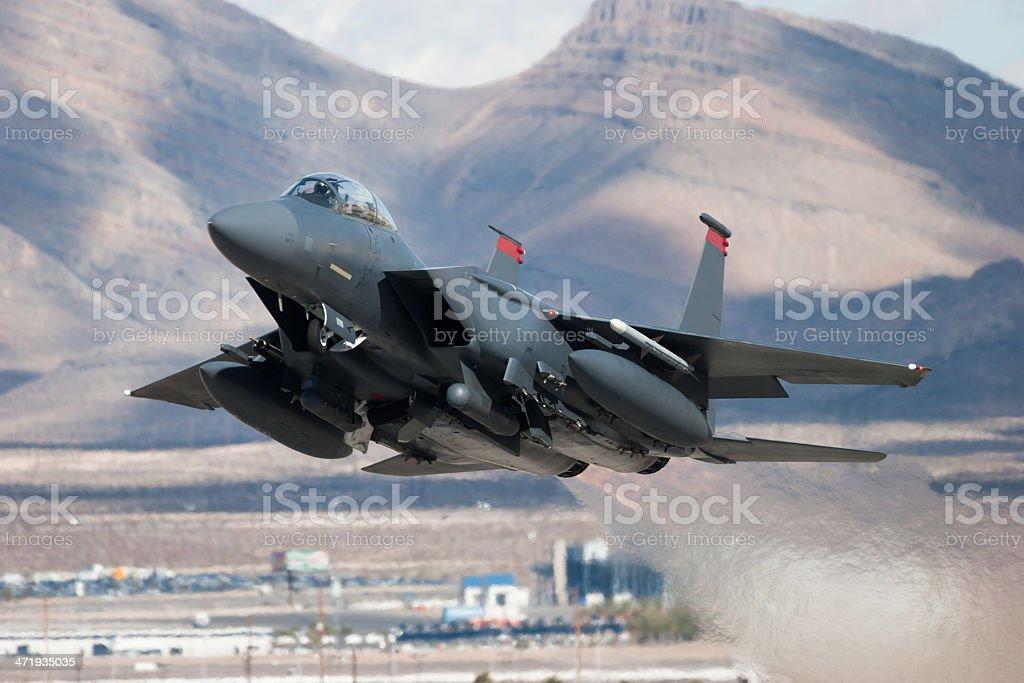 F-15E Strike Eagle flying past mountains stock photo