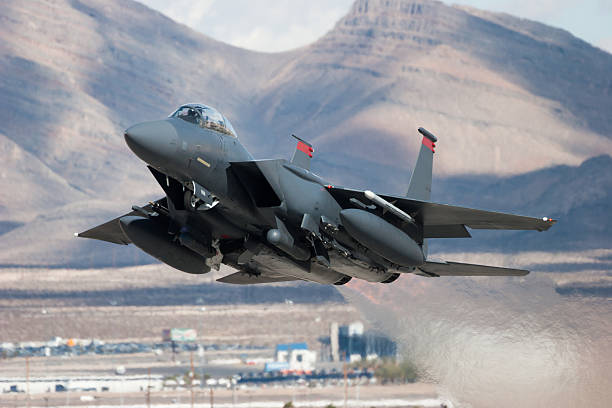 F-15E Strike Eagle flying past mountains An F-15E Strike Eagle taking off. military airplane stock pictures, royalty-free photos & images