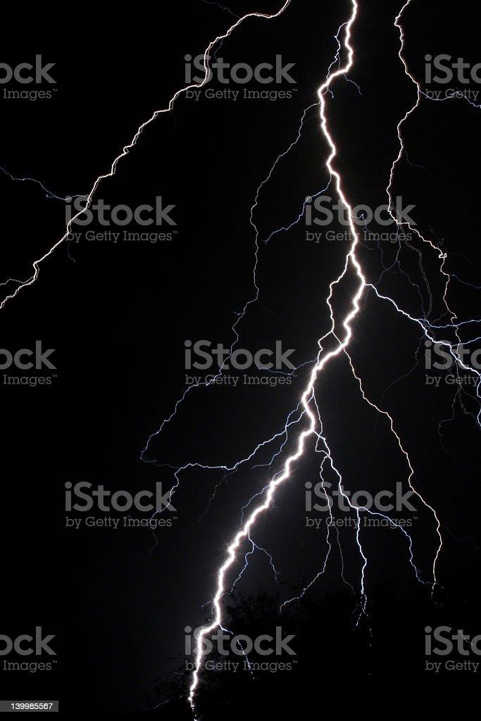 A strike of lightening lighting up the night sky royalty-free stock photo