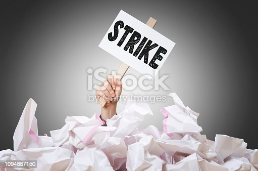 Strike! placard in hand with crumpled paper pile. Employees going on strike concept.