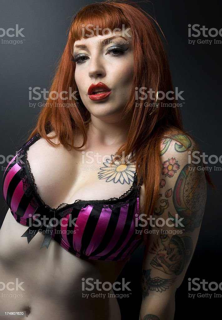 Striking Female Tattoo Goth Pin Up With Long Orange Hair royalty-free stock photo