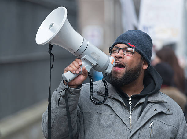 NSGEU Striking Nurse with Megaphone Halifax, Canada - April 3, 2014: A striking Nova Scotia Government & General Employees Union nurse uses a megaphone to voice his opinion outside Province House after walking out on a legal strike when talks with the union and Capital Health reached a stalemate in contract talks primarily relating to the union's demands for lower nurse-to-patient ratios. activist stock pictures, royalty-free photos & images