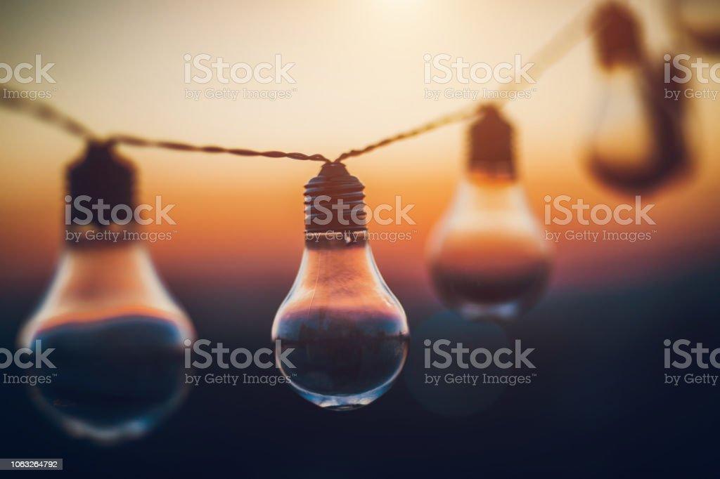 String light bulbs at sunset stock photo