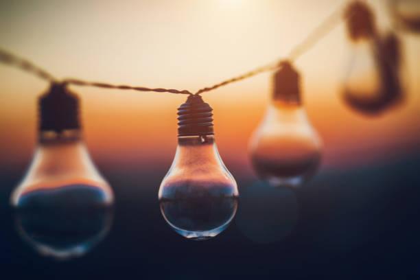 zeichenfolge glühbirnen bei sonnenuntergang - terrassen lichterketten stock-fotos und bilder
