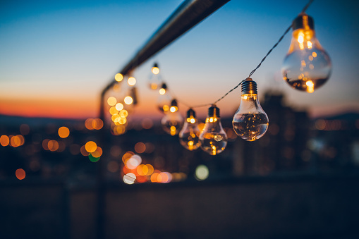 Close up picture of a string light bulbs at sunset on the rooftop.