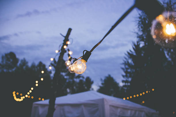 String Lights at an outdoor event globe bulb string lights hanging at an outdoor event at dusk entertainment tent stock pictures, royalty-free photos & images