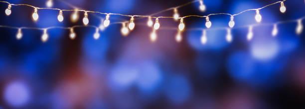 reeks gloeilampen op blauwe abstracte achtergrond - snoerverlichting stockfoto's en -beelden