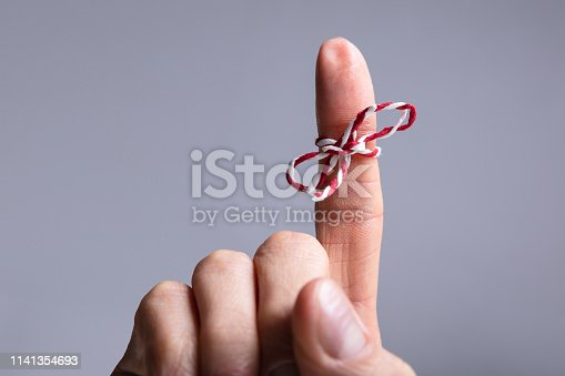 Close-up Of Person's Finger With Tied Ribbon Bow Over Gray Background
