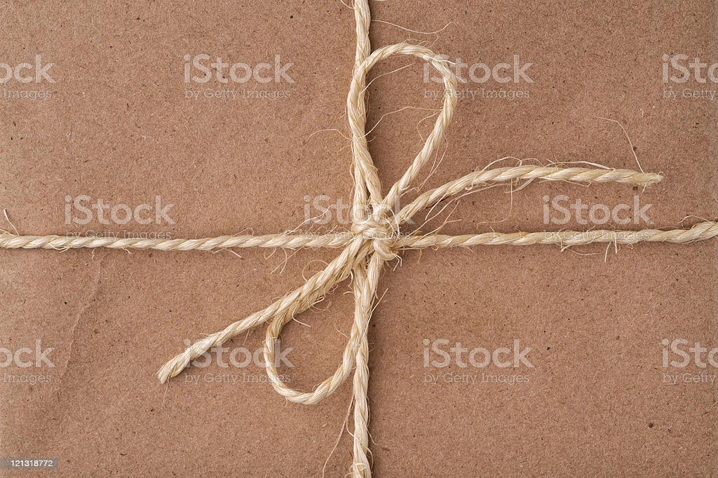 String tied in bow, on a brown recycled paper package stock photo