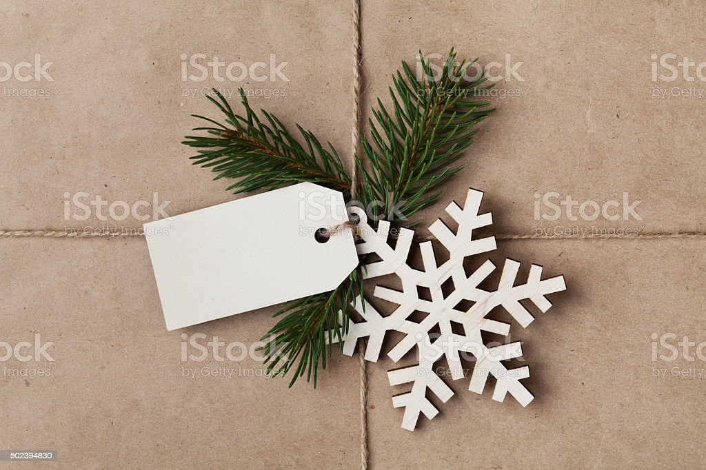 String tied iwith tag, fir tree and wooden snowflake stock photo