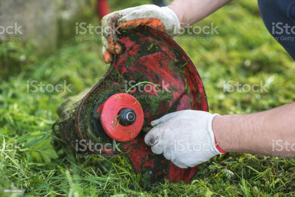 String trimmer cleaning after cutting the grass, workflow foto de stock royalty-free