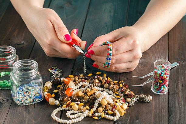 stringing beads on the needle stock photo