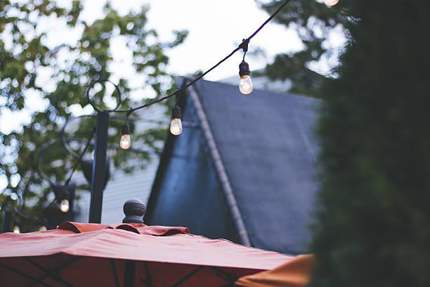 strings lights on an outdoor restaurant patio - terrassen lichterketten stock-fotos und bilder