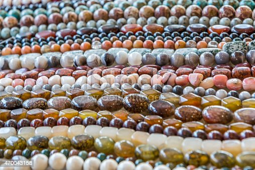 Assorted strings of gem stones beds over