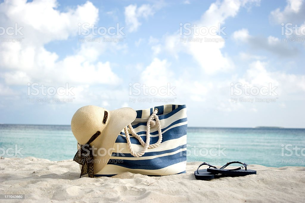 Striped beach bag with straw hat and flips flops on beach stock photo