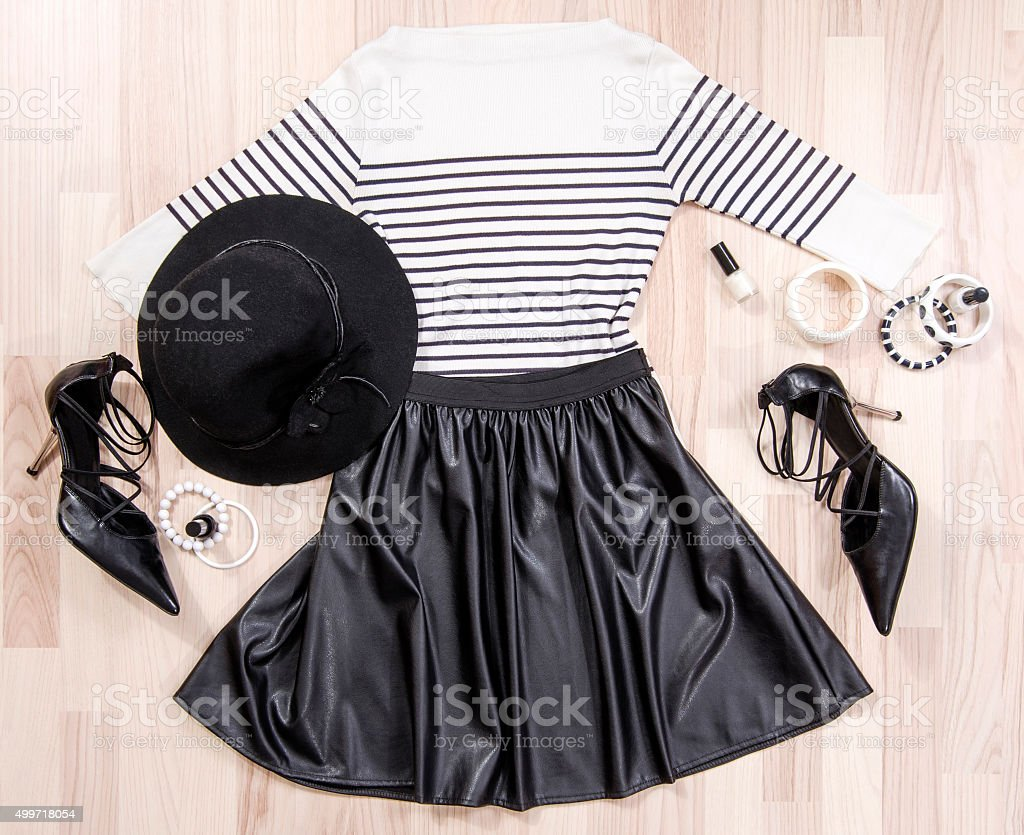 Striped blouse and leather skirt arranged on the floor. stock photo