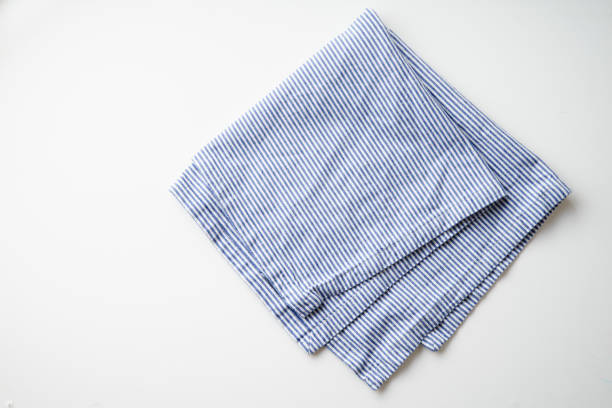 randig blå och vit textil servett vikta på vit bakgrund. mat stylingelement - servett bildbanksfoton och bilder