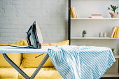 istock striped blue shirt and iron on ironing board at home 965557918