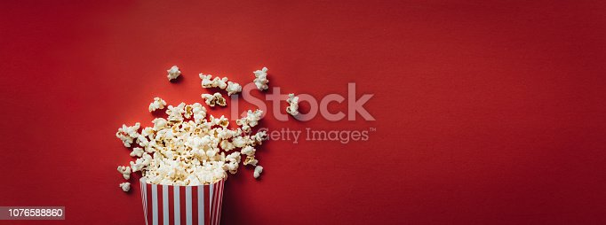 Striped box with popcorn on red background. Wide format, banner