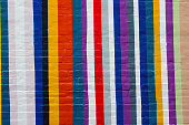 Painted colorful stripes on an exposed brick wall in white, blue, pink, black, blue, yellow, red and purple