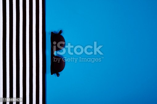Summer and vacation concept. Top view of striped clothes and sunglasses on blue  colored  trendy color background .Fasionable trendy concept. Color of the year 2020.