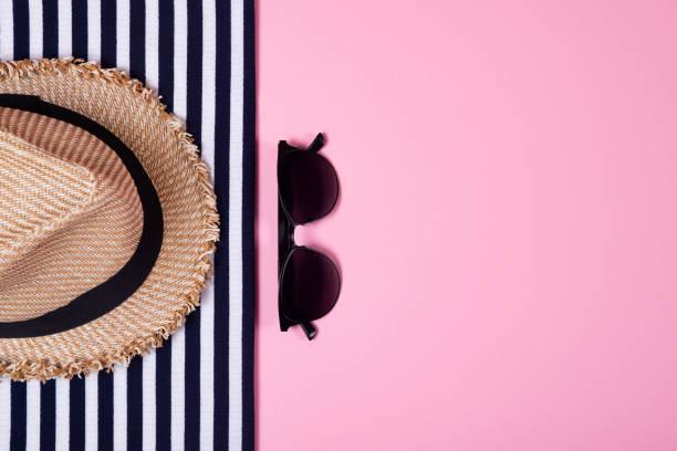 Gestreifte Kleidung, Sonnenbrille und Strohhut auf rosa Hintergrund. Ansicht von oben. Flach zu legen. – Foto