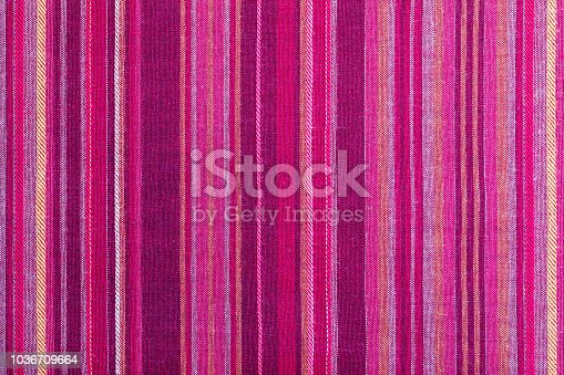 Striped fabric texture with multiple warm colors (purple, purple, magenta, pink, red, maroon, orange, yellow). Close-up of the tissue. Ethnic aspect
