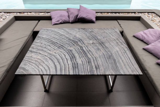 Striped granite dining table with pillow on sofa at side swimming pool stock photo