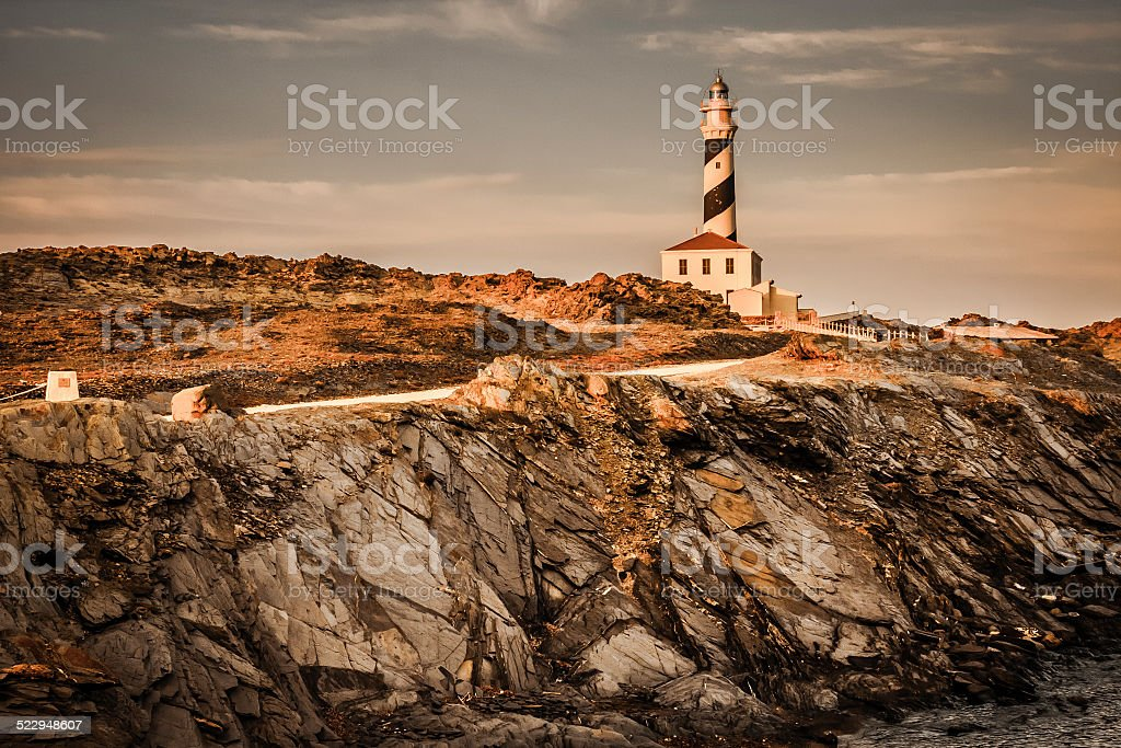 Striped Lighthouse on top of a rock cliff stock photo