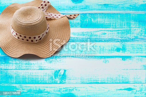 699960484istockphoto Striped retro hat flat-lay, top view, wide composition - Summer concept on wooden blue Backgrounds 1004276846
