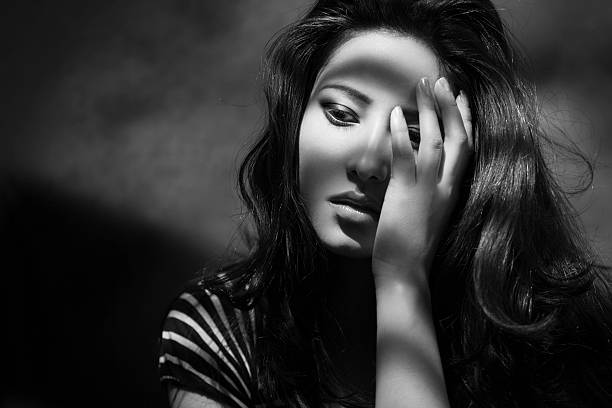 Striped shadows on beautiful sad young woman holding her head. stock photo