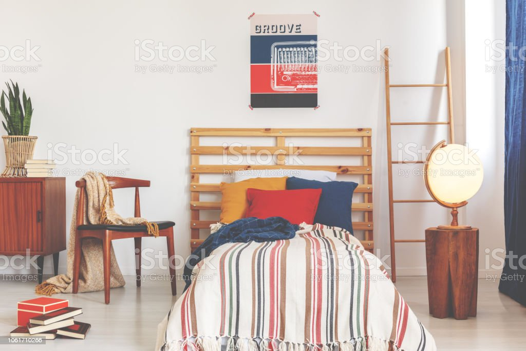 Striped sheets on wooden bed between ladder and chair in retro bedroom interior with poster. Real photo stock photo