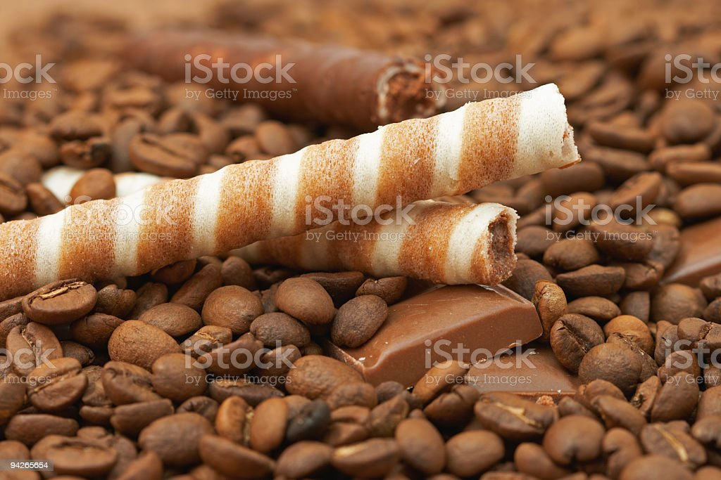Striped wafer rolls, chocolate and coffee beans royalty-free stock photo