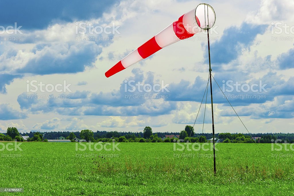 striped windsock in a green field stock photo