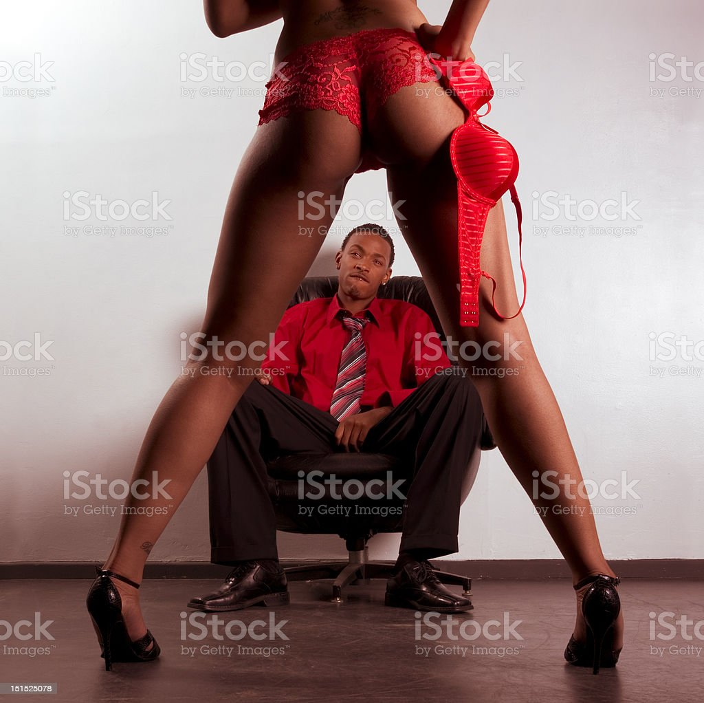 Striper woman in red dancing for young black man stock photo