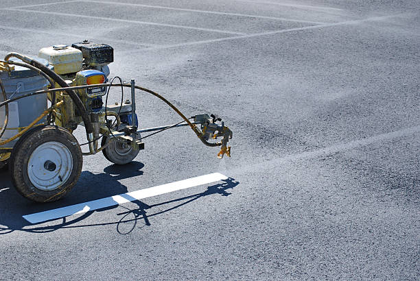 Striping Lines onto fresh asphalt Striping machine painting lines onto fresh asphalt. parking lot stock pictures, royalty-free photos & images