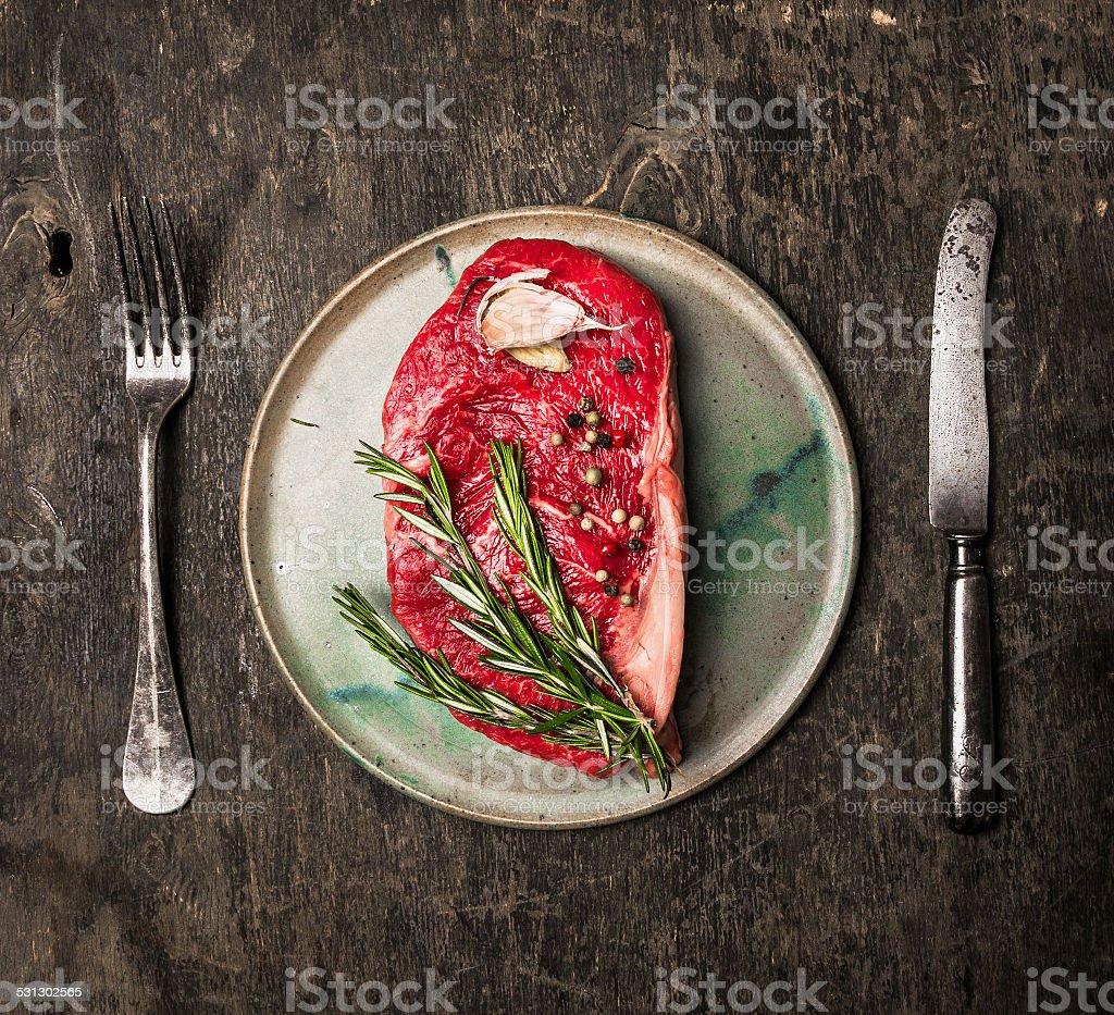 Striploin Steak on  plate with rosemary, garlic, salt and pepper stock photo