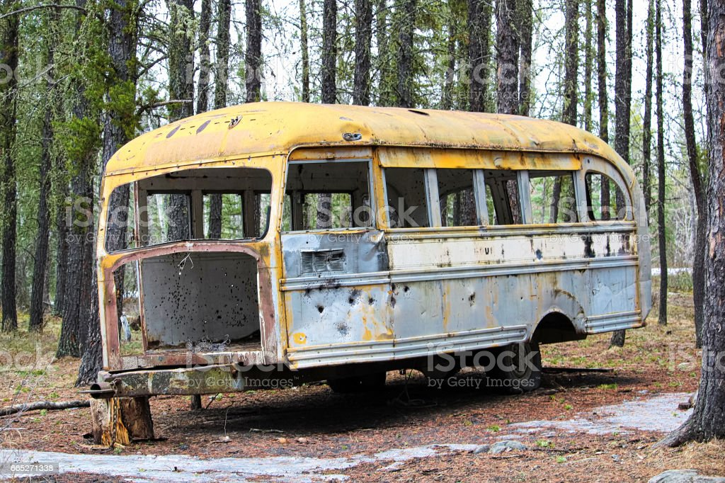 Stripped abandoned bus at a hunters camp on crown land stock photo
